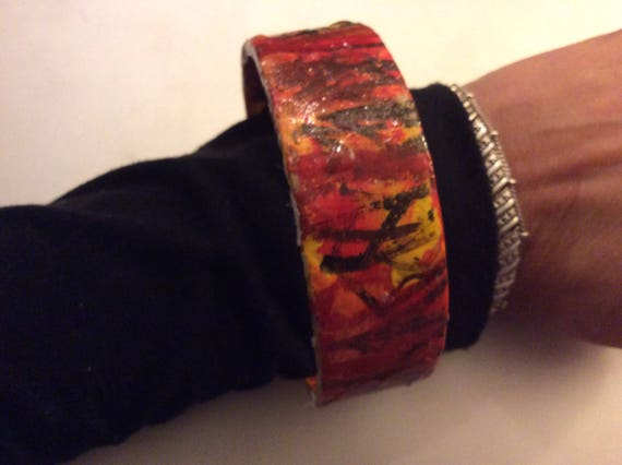 Braclet  painted in red,yellow,orange and black acrylic paint at the sunset forset wearable art ,all season made in ny  longisland
