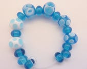 Beads, Lampwork Glass bead set consisting of 17 beads in beautiful transparent aqua blue  with white  highlights. SRA artisan