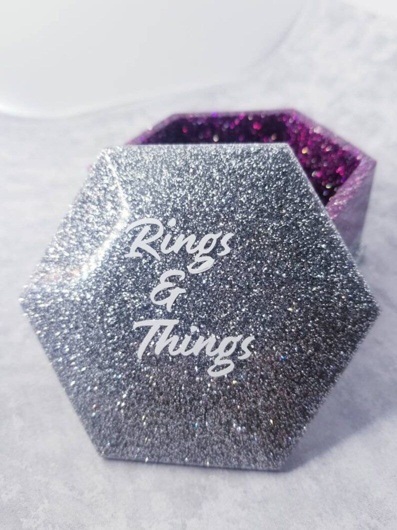 2.75 wide X 1.75 tall Hot pink and silver glitter hexagon shaped resin jewelry box with lid reading Rings /& things