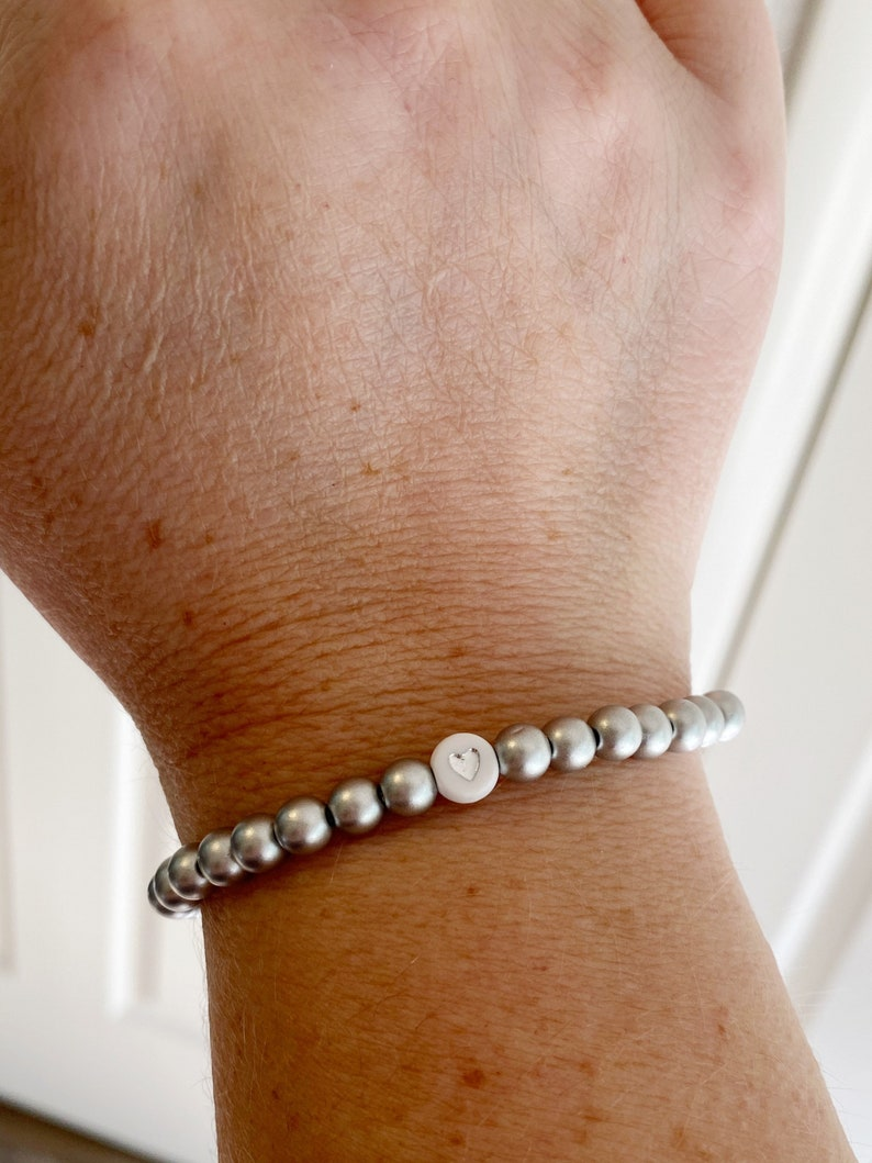 Silver beaded stretchy bracelet with white and silver heart bead