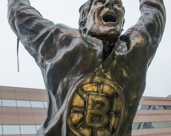 Four photographs of the Bobby Orr Bronze Statue at TD Garden