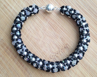"""7"""" Opal and Silver 4mm beads covered in black crystal seed bead netting."""