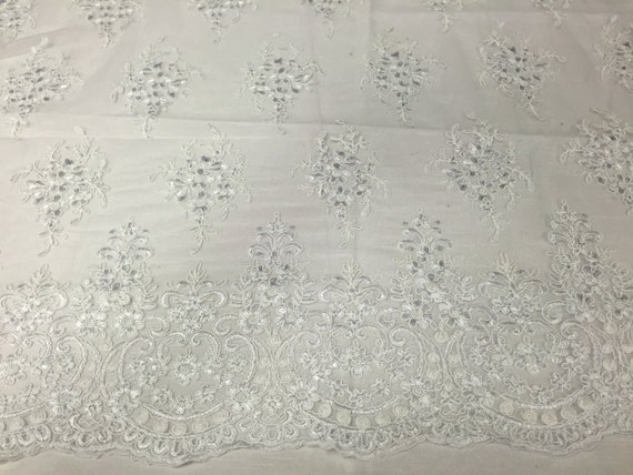 White Royal flowers design embroider with sequins and corded on a mesh lace-yard