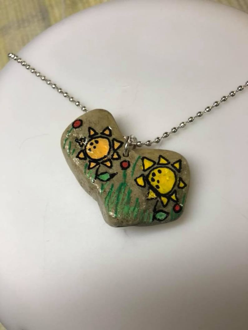 Heart shaped rock drilled in the center with abstract sunflowers in grass with red posies made into a pendant on a sterling chain.