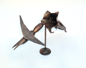 Hummingbird Sculpture.  Hand forged steel humming bird and trumpet flower.  Natural finish/patina with clear top coat. Spins on base.