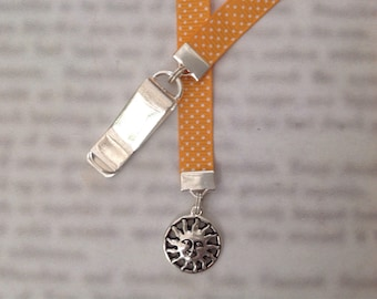 Sun face bookmark - Attach clip to book cover then mark the page with the ribbon. Never lose your bookmark!