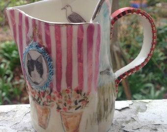 Beautiful handmade Porcelain Jug, Illustrated with lovely things ..cat, bird, pots of flowers & the seaside, presented in an attractive box