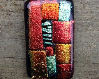Beautiful handmade fused diachroic glass pendant with a silver plated bail in a vibrant patchwork of changing colour.