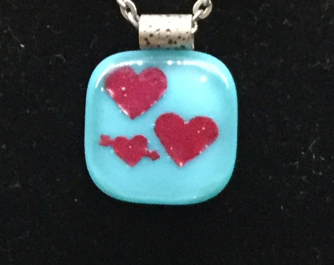 Turquoise color glass pendant with 3 copper hearts.  Pendant is just under 1 inch square with 18 inch antique silver chain. Nickel free