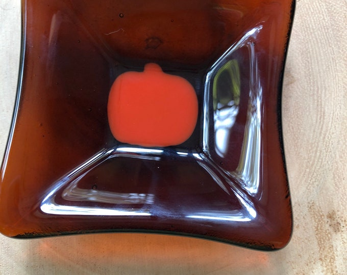 "Fused glass dish, pumpkin dish, trinket dish.  Light brown transparent background.  Measures 3 1/8"" square."