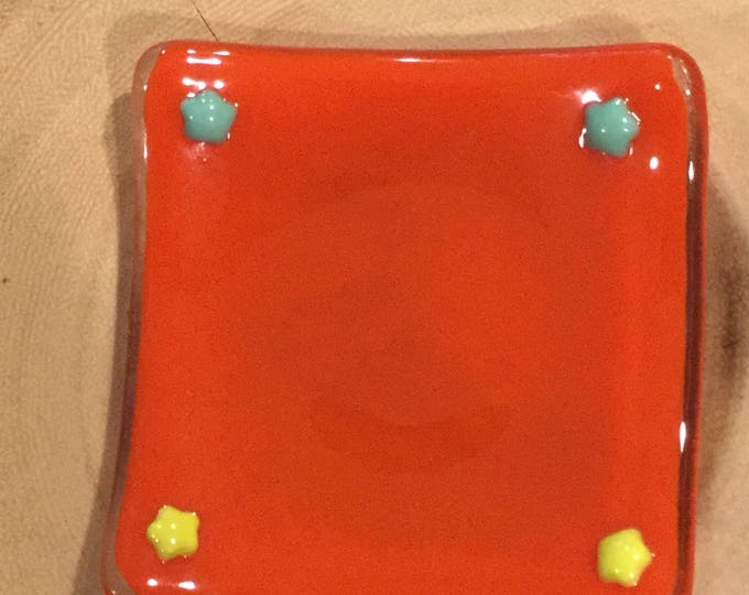 Glass dish with slightly curved edges in a beautiful rich orange with sage green and yellow stars on the edges. Sushi style.