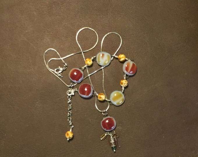 Charm bracelet and matching necklace in a variety of brown's.  Fused glass squares wire wraped with beads and charms.
