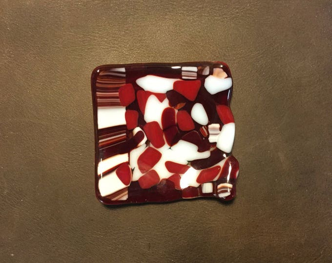 Glass plate, red kalidascope trinket dish.  This beautiful dish is small measuring 3 1/4 inch square and has slightly flanged edges.