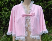 Vintage 1960s, 1970s pink nylon, chiffon bed jacket with ribbon and white ruffles. Nightwear, lingerie, boudoir, glamour.