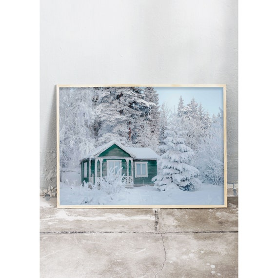 Art print of tiny, green, fairytale cottage in the woods covered in snow. Print printed on high quality, matte paper.