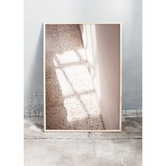 Art photography print of sunshine and shadowily on a beige floor and wall. Print is printed on a matte, high quality paper.