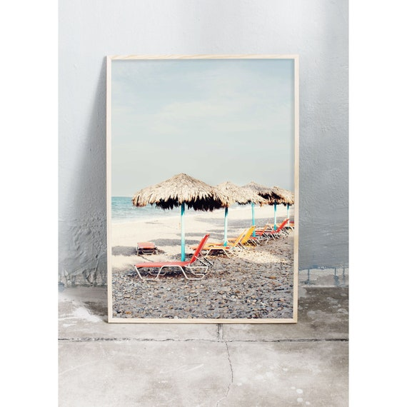 Photography art print of orange sun chairs on the beige beach on Crete in Greece. Print is printed on a high quality, matte paper.