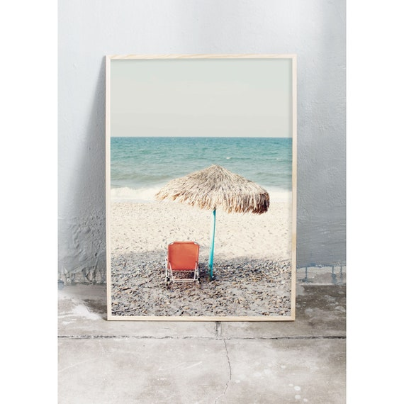 Photography art print of orange sun chair on the beige beach by the turquoise ocean on Crete. Printed on a high quality, matte paper.