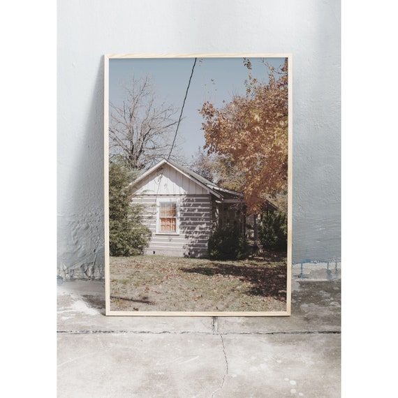Photography art print of a gray house with orange curtain. Print is printed on a high quality, matte paper.
