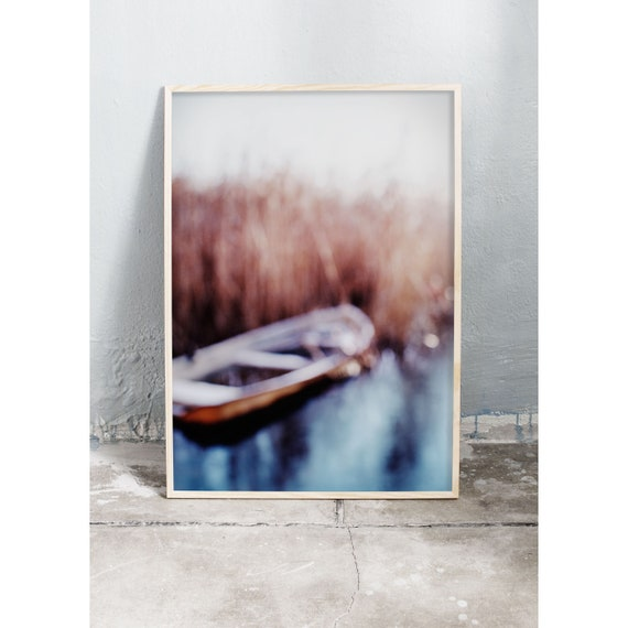 Abstract photography art print of boat, icy water and common reed by a lake. Print is printed on a high quality, matte paper.
