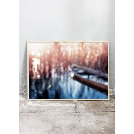 Abstract photography art print of icy water, a boat and common reed by a lake. Print is printed on a high quality, matte paper.