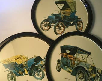 Three metal trays featuring antique automobiles - for serving or wall decor