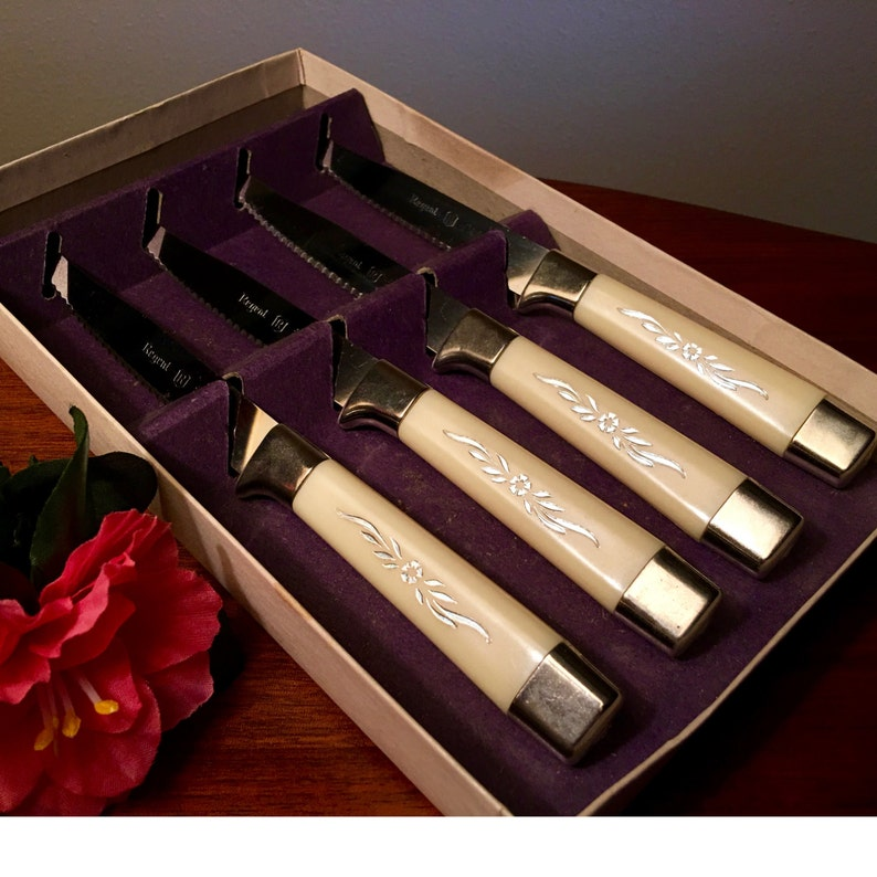 Set of four Regent Stainless steak knives with silver inlays