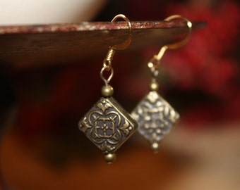 Bronze floral diamond-shaped dangle earrings.