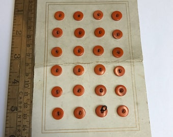 Card of small orange vintage buttons