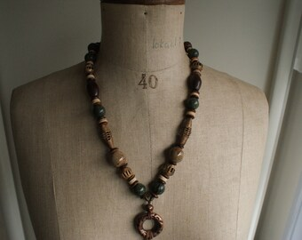 Long brown-coloured necklace with copper coloured ring, Shia note, porcelain beads