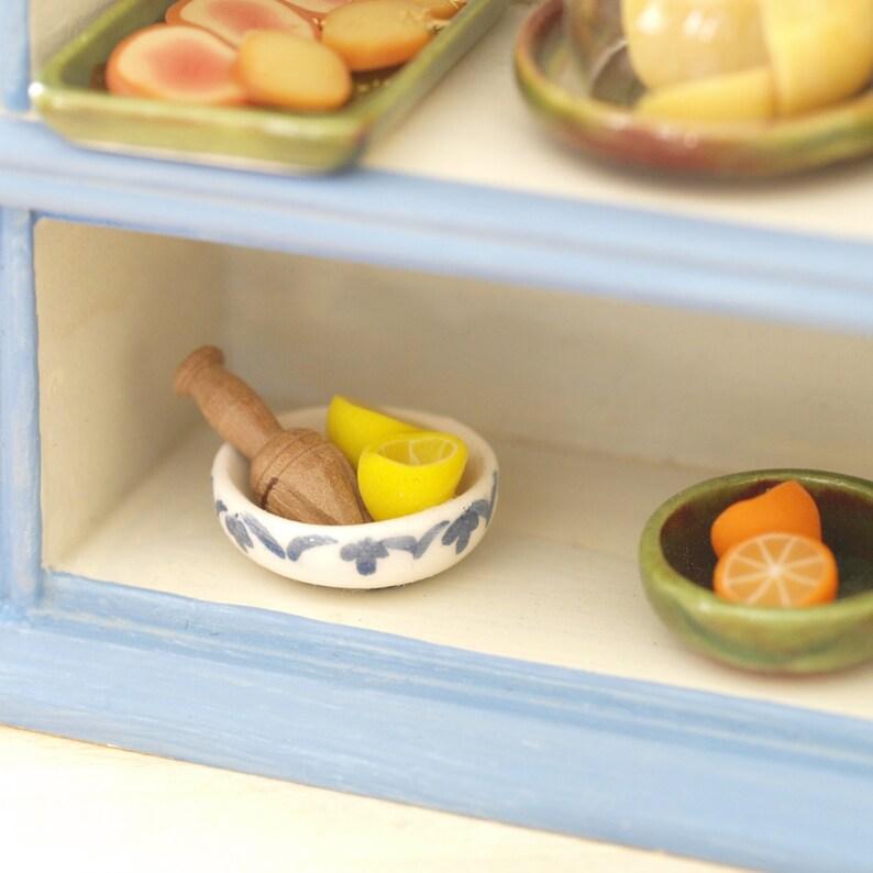 Ceramic bowl with oranges or lemons and juicer wooden image 0