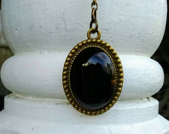 Shiny Black Onyx Cabachon Pendant in Antique Brass Setting hung from 24 inch Antique Brass Beaded chain, 25 x 18mm cabachon