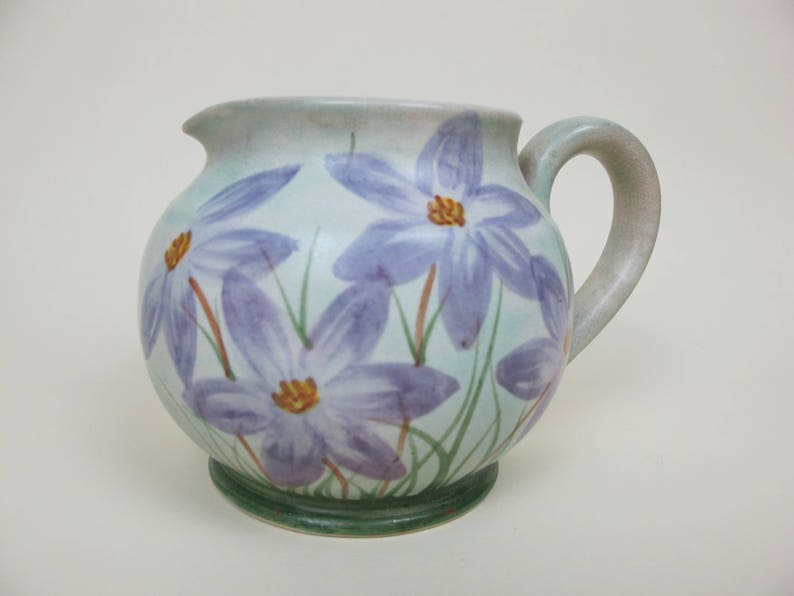 Vintage studio pottery hand painted jug Pale green background with large purple daisy like flowers Signed E Radford Lovely shape.