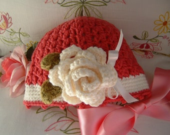 Crochet baby hat in dark pink and white wool with a rose applied. Children's fashion Idea winter. Romantic and feminine style