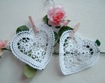 Two white heart-shaped crochet lace centers. Crochet house in romantic style. Hearts of Lace. White cotton decoration.