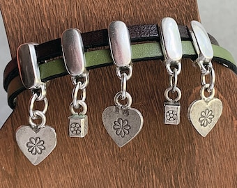 Flat Leather Olive Green and Brown strands hold 5 sliders with Cube and Heart Hill Tribe Charms stamped with Flowers and Magnetic Clasp