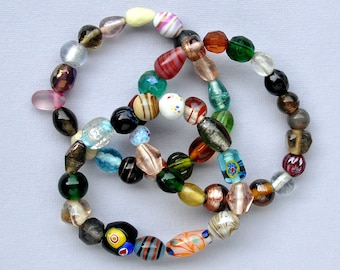 Three stretchy bracelets made of European glass beads in a wide variety of colors, shapes, sizes and decorative techniques