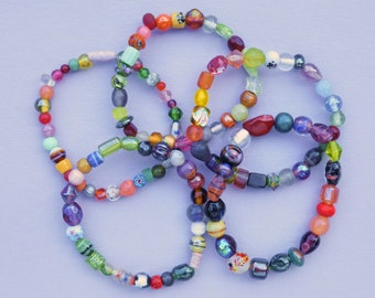 Five stretchy bracelets made of European glass beads in a wide variety of colors, shapes, sizes and decorative techniques