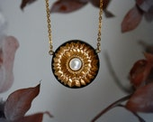 Lopha necklace - Circular pendant made from black sand, gold pigments and freshwater pearl on gold plated chain