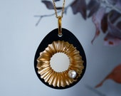 Anomia large teardrop statement necklace made from black sand, gold pigments and freshwater pearl on gold chain