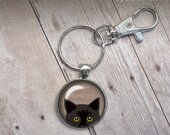 Peeking Black Cat Keychain Key Chain Tan background yellow eyes black bombay cute glass dome photo illustration trendy popular gift under 20
