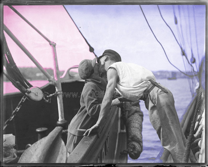 1930 Vintage Photograph: Man and Woman Kissing Across Two image 0