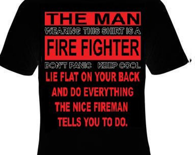 the man wearing this T shirt is firefighter dont panic keep cool lie flat on your back and do everthing the nice fireman fire fighter
