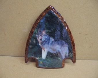 Wolf in the trees, photo on an arrowhead plaque.