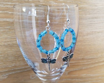 Round beaded earring with red and blue seed beads mix with a dragonfly charm