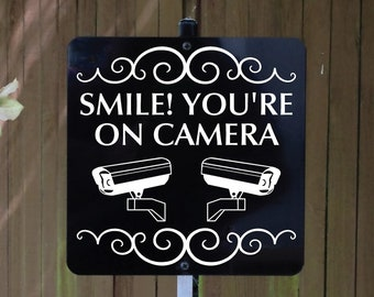 Smile! You're On Camera Metal Sign attached to sturdy yard stake. Free Shipping