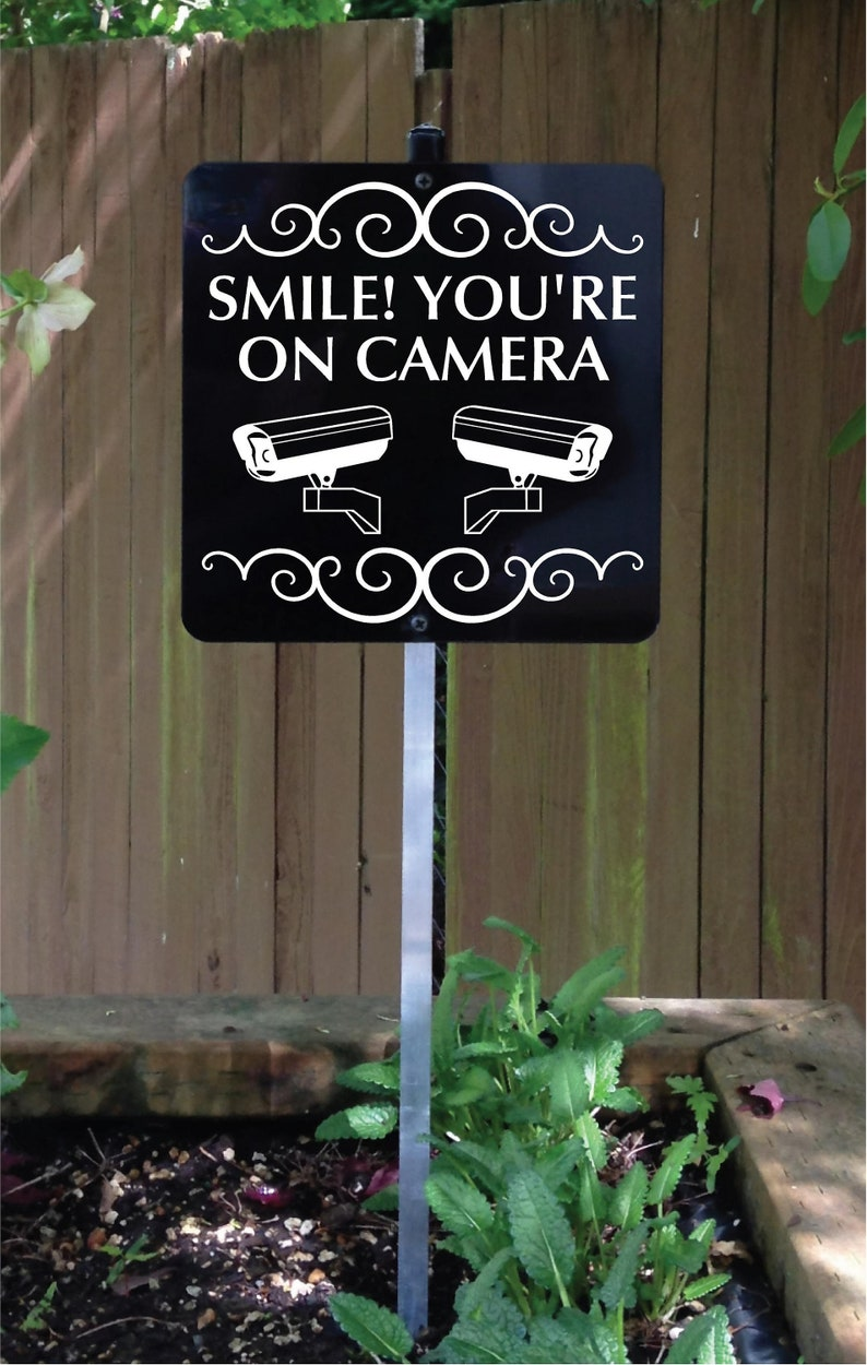 Smile You're On Camera Metal Sign attached to sturdy yard image 0