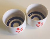 Pair Bullseye Sake Tasting Cups Japanese Import Ceramic Kotobuki Style Porcelain Japan Orange Five Petal Flower Logo