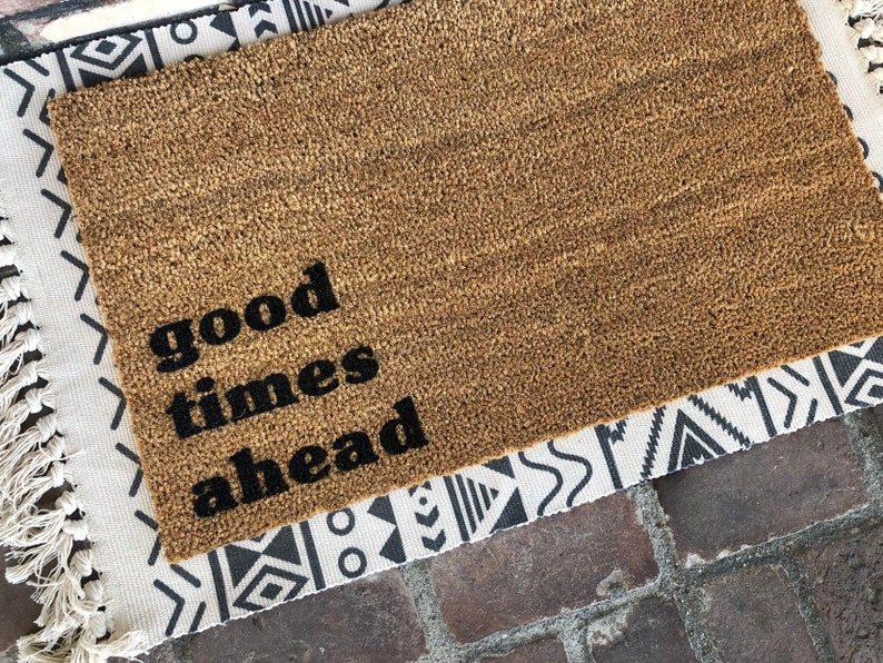 Good Times Ahead Doormat layered over a pretty Navajo patterned rug makes a charming impression at the front door. Come discover more French Farmhouse Decor inspired by Fixer Upper and click here to Get the Look of The Club House Kitchen & Sun Room. #fixerupper #joannagaines #kitchendecor #frenchfarmhouse