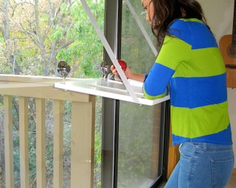 """White Standing Desk attaches to window surfaces with heavy duty suction cups 